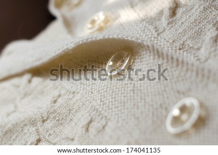 Detail of woven handicraft knit woolen design texture and button. Fabric white background - stock photo
