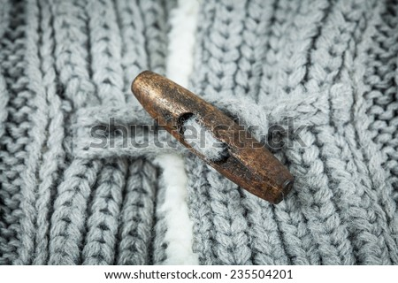 Detail of woven woolen design texture and button. Fabric grey background  - stock photo