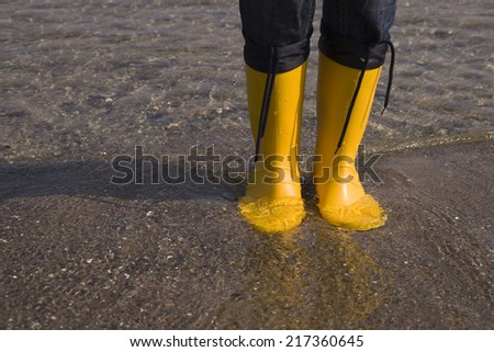 Detail of yellow boots standing in water at the beach - stock photo