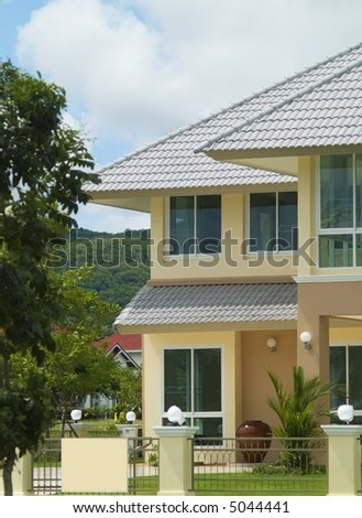 Detail of yellow, luxury villa with two floors in beautiful, natural setting.