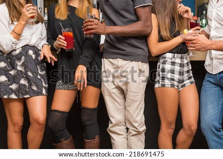 Detail of young friends having fun in a bar drinking cocktail. - stock photo