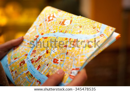 Detail of young tourist hands holds city map to trying navigate using map in Venice city maze on her holidays - stock photo