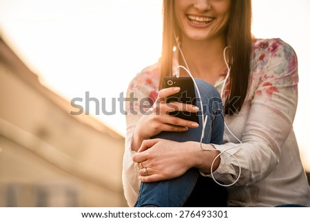 Detail of young woman listening music from her phone and singing in street with sun in background - stock photo