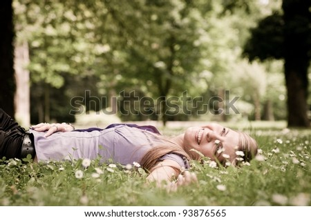 Detail of young woman lying in fresh green grass with flowers - low angle view