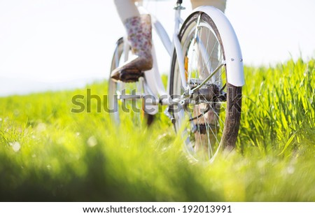 Detail of young woman's feet in boots riding on bike in green field - stock photo