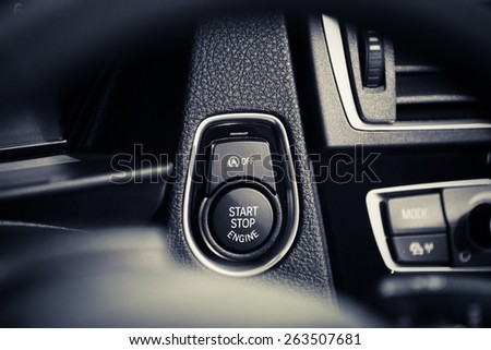 Detail on a black start button in a car. - stock photo