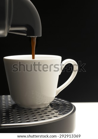 Detail on black background a coffee machine with nice cup - stock photo