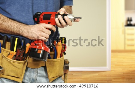 detail on handyman manual worker, tools belt and red drill in his hands