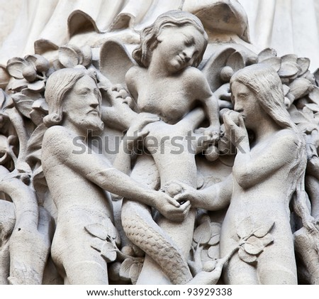 Detail on Notre Dame de Paris Cathedral fachade: Adame, Eve and the forbidden apple - stock photo