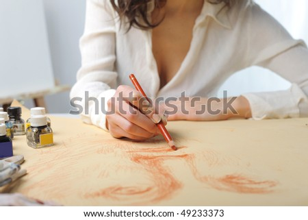 Detail on the hands of a woman painting - stock photo