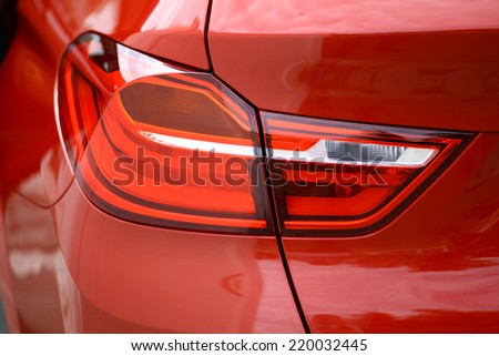 Detail on the rear light of a red car. - stock photo