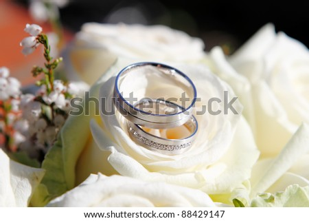 Detail on wedding rings with white flowers - stock photo