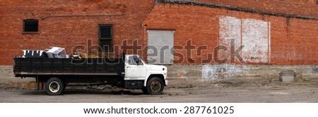 Detail panorama of work truck and brick wall - stock photo