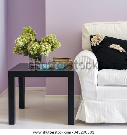 detail pf fabric sofa and small table with a vase of Hydrangea on the top in the living room - stock photo
