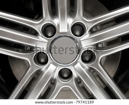 Detail photo of a car rim with lug nuts and brake disc - stock photo