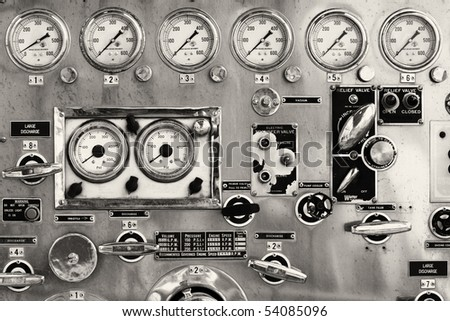 Detail photo of the instrument panel of an old firetruck displaying the various gages and levers .