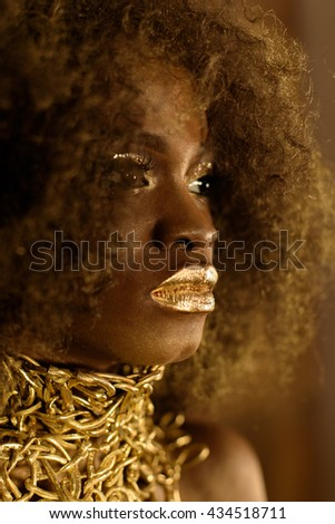 Detail portrait of an African American woman with golden makeup and accessories - stock photo
