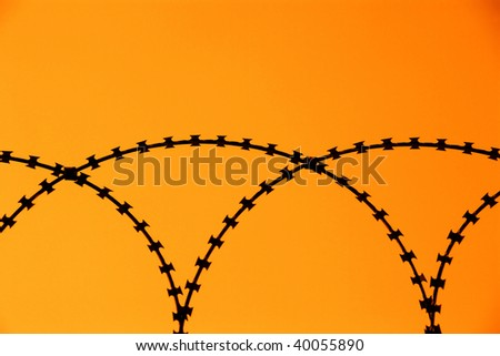 detail shot from a barbed wire fence with orange sky - stock photo