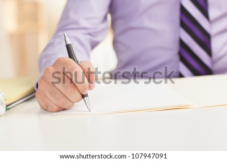 Detail shot of a business man writing on paper using pen wearing a purple shirt and tie - stock photo