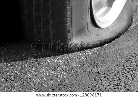 Detail Shot of a Flat Tire on a Car - stock photo