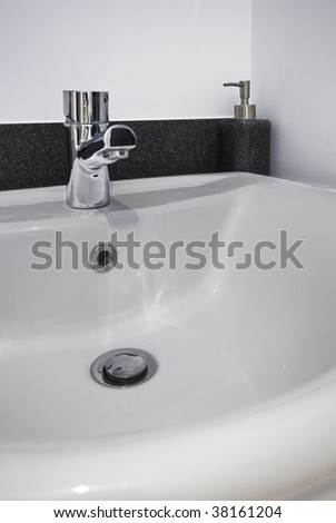 detail shot of a modern ceramic hand wash basin with chrome water mixer tap - stock photo