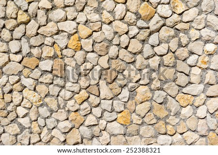 Detail shot of a natural stone wall of medium-sized, beige and yellow stones, taken in Germany   - stock photo