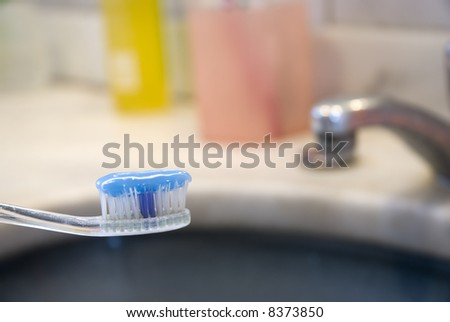 Detail shot of a tooth brush with tooth paste on it and basin in the blurred background