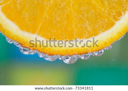 Detail shot of an orange slice with bubbles on green background