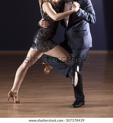 detail shot of couple in formal wear tango dancing