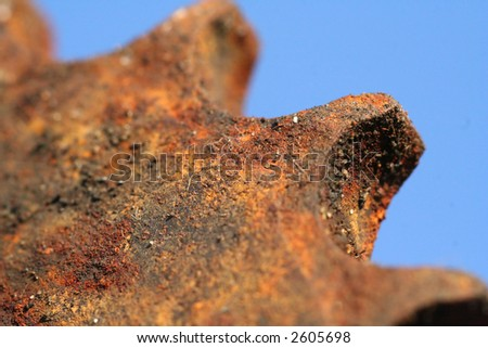 Detail shot of rusty cog or sprockett, short depth of field on a blue background - stock photo