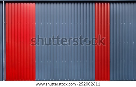 Detail shot of the facade of an industrial building with vertical, blue and red metal profile.  - stock photo