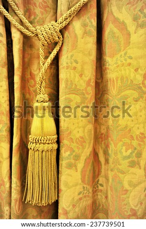 Detail shot with a yellow curtain decorative tassel