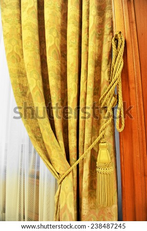 Detail shot with a yellow curtain decorative tassel - stock photo