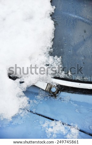 Detail shot with an old car windshield wiper covered in snow