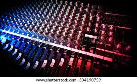 detail sound mixer in red and blue light with great perspective, the version with beveled edges into the black - stock photo