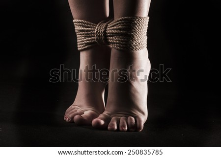 detail suspended bound feet submissive young girl on a black background / BDSM theme - stock photo