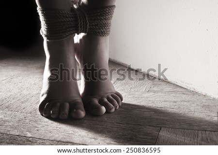 detail suspended bound feet submissive young girl on the floor / BDSM theme - stock photo