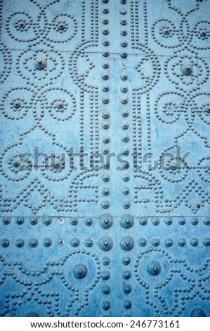 Detail take of an old door studded with geometric motives - stock photo