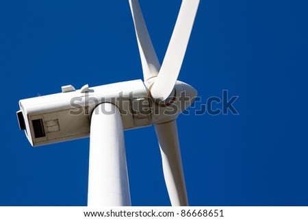 detail top of a windmill for electric power production against blue sky