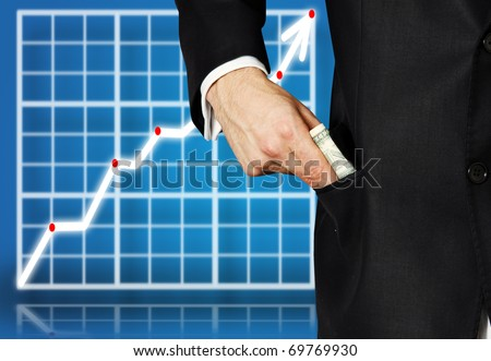 Detail view of a business man putting money into pocket - stock photo