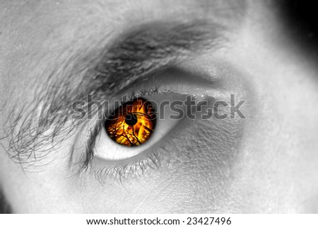 Detail view of a male eye with flames instead of the iris. - stock photo