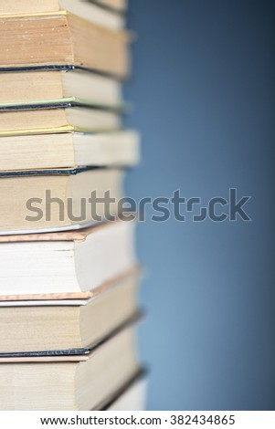 Detail view of a pile of books, on textured blue background. Clear space at right