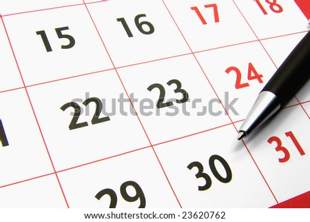 Detail view of a typical calendar with a pen. - stock photo
