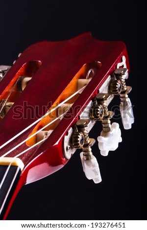 Detail view of fingerboard on classical acoustic guitar, over black background. - stock photo