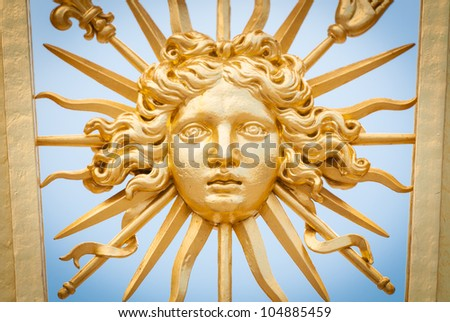 Detail view of golden ornate gate of Chateau de Versailles depicting human face. Blue sky in background. Paris, France, Europe. - stock photo
