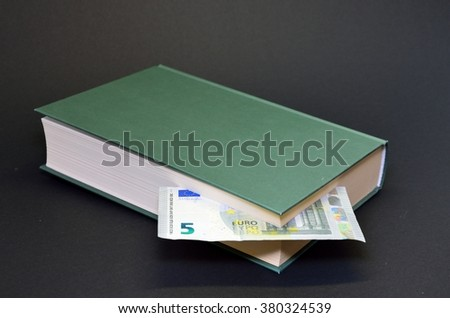Detail view of green book with euro money inside on black background - stock photo