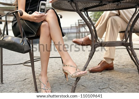 Detail view of two business people's legs under a coffee table while in a meeting outdoors, using a cell phone. - stock photo
