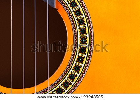 Detail view of yellow wooden classical acoustic guitar. - stock photo