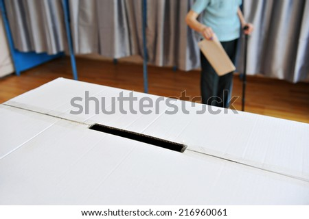Detail with a ballot box and an old person in cane coming out from the vote cabin in the background - stock photo