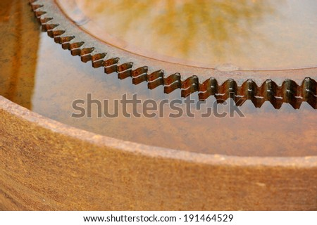 Detail with a rusty industrial sprocket wheel - stock photo
